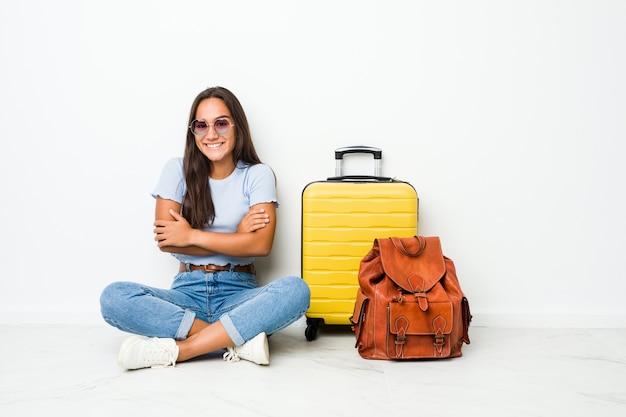Giovane donna indiana di razza mista pronta ad andare in viaggio che si sente sicura, incrociando le braccia con determinazione.