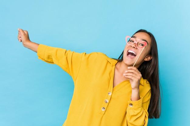 Giovane donna indiana divertendosi e giudicando gli oggetti di un partito isolati