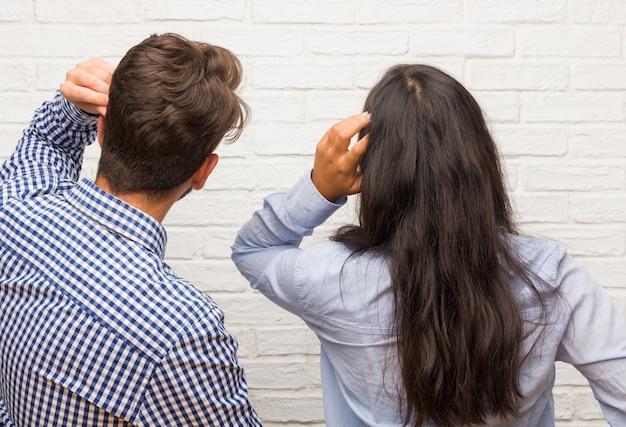 Giovane donna indiana e coppia uomo caucasico che mostra indietro, in posa e in attesa, guardando indietro