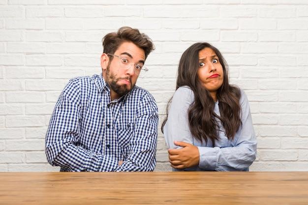 Giovane donna indiana e coppie caucasiche dell'uomo che dubitano e che scrolla le spalle le spalle