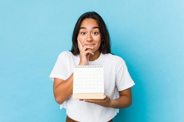 Giovane donna indiana felice giudicando un calendario isolato