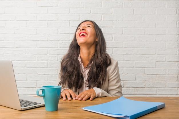 Giovane donna indiana in ufficio ridere e divertirsi, essere rilassato e allegro
