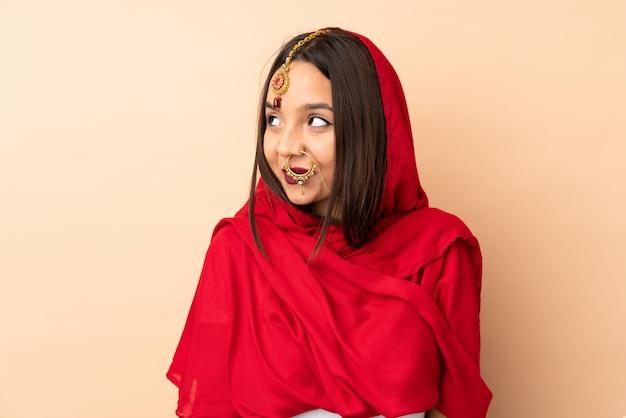 Giovane donna indiana isolata su beige che ha dubbi mentre osservando in su