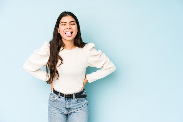 Giovane donna indiana isolata sulla lingua blu divertente e friondly che attacca fuori.