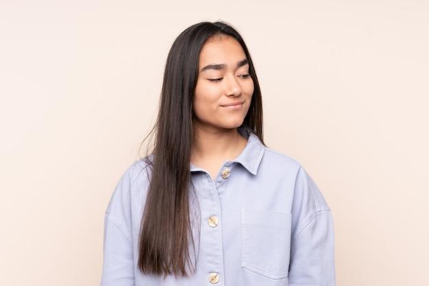 Giovane donna indiana isolata sulla parete beige che ha dubbi mentre osservando lato