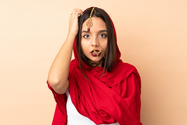 Giovane donna indiana isolata sulla parete beige con un'espressione di frustrazione e non comprensione