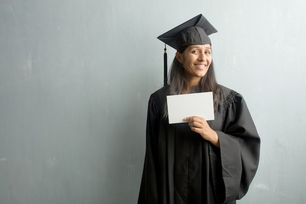 Giovane donna indiana laureata contro un muro allegro e con un grande sorriso, fiducioso, cordiale e sincero