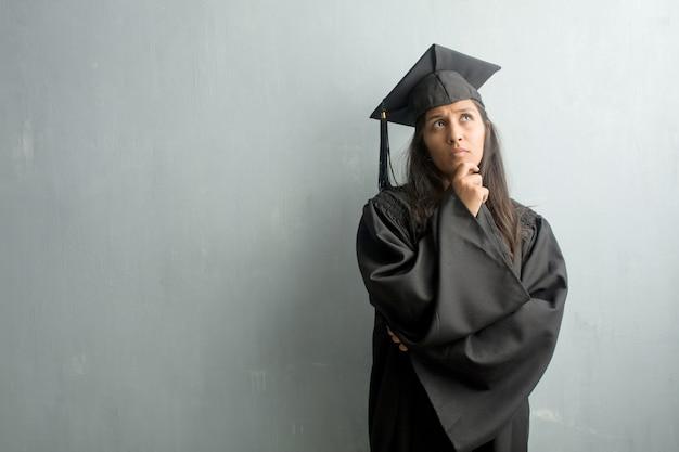 Giovane donna indiana laureata contro un muro dubitando e confuso