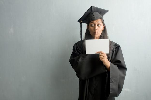 Giovane donna indiana laureata contro un muro mantenendo un segreto o chiedendo il silenzio