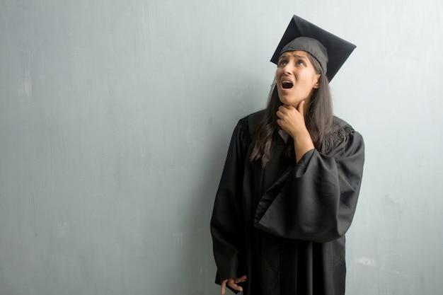 Giovane donna indiana laureata contro un muro preoccupato e sopraffatto, ansioso sensazione di pressione, concetto di angoscia