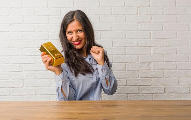 Giovane donna indiana molto felice ed eccitata, alzando le braccia, celebrando una vittoria o successo, vincendo la lotteria