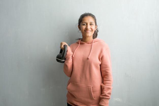 Giovane donna indiana sportiva contro un muro allegro e con un grande sorriso