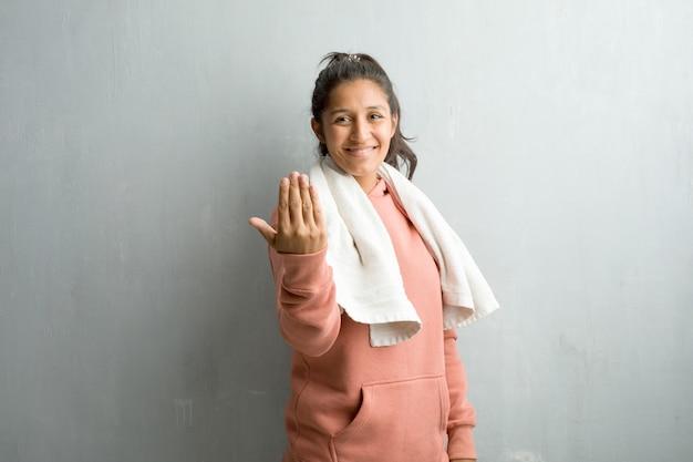 Giovane donna indiana sportiva contro un muro che invita a venire
