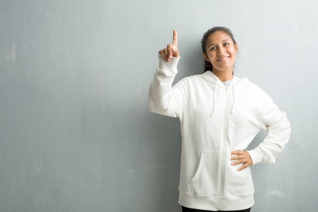 Giovane donna indiana sportiva contro una parete della palestra che mostra numero uno