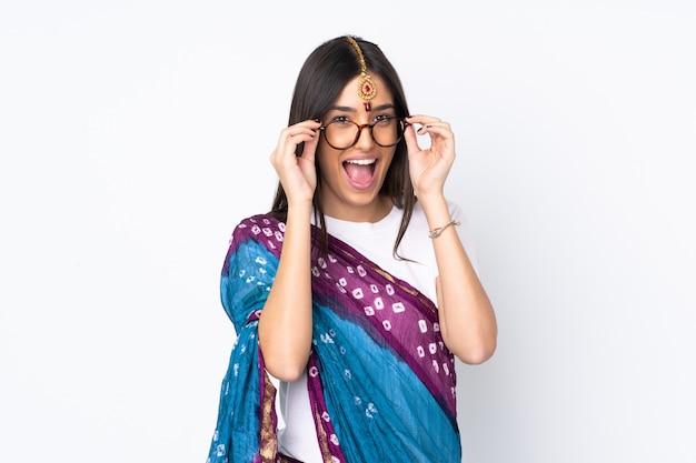 Giovane donna indiana su bianco con gli occhiali e sorpreso