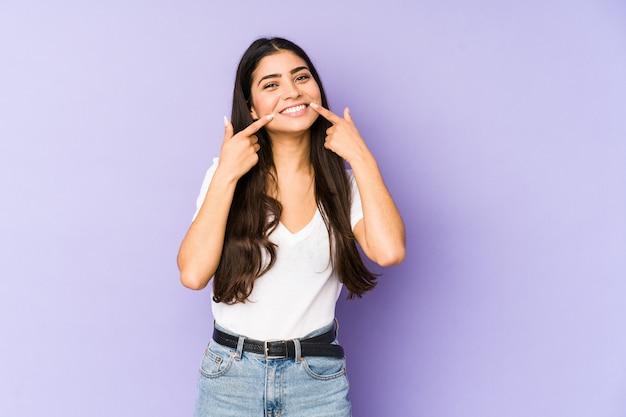 Giovane donna indiana sui sorrisi viola della parete, indicando le dita alla bocca.