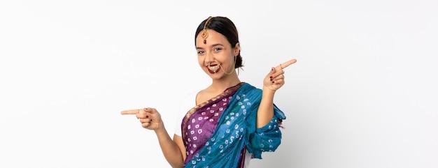 Giovane donna indiana sul muro bianco che punta il dito verso i laterali e felice
