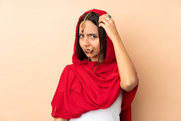 Giovane donna indiana sulla parete beige che ha dubbi mentre si gratta la testa