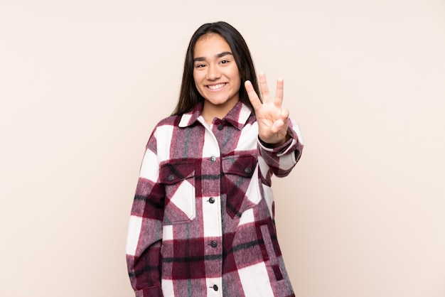 Giovane donna indiana sulla parete beige felice e contando tre con le dita