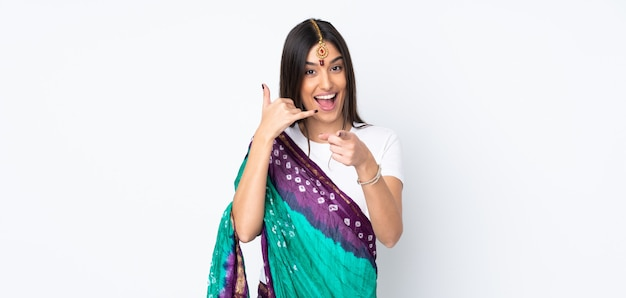 Giovane donna indiana sulla parete bianca che fa gesto del telefono e che indica parte anteriore