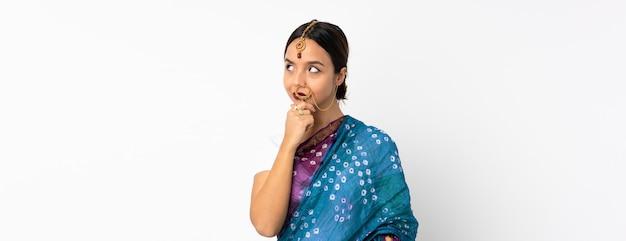 Giovane donna indiana sulla parete bianca che ha dubbi e con espressione del viso confuso