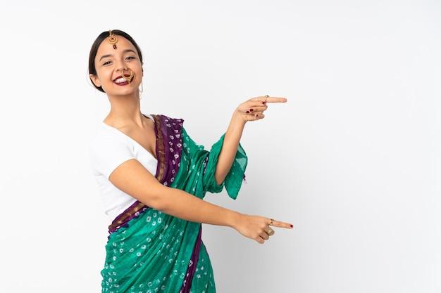 Giovane donna indiana sulla parete bianca che punta il dito verso il lato e che presenta un prodotto