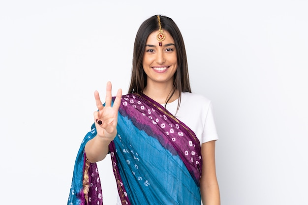 Giovane donna indiana sulla parete bianca felice e contando tre con le dita