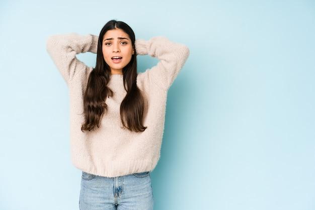 Giovane donna indiana sulla parete blu che grida con rabbia.