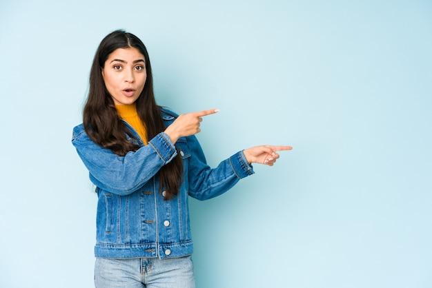 Giovane donna indiana sulla parete blu che indica con gli indici uno spazio