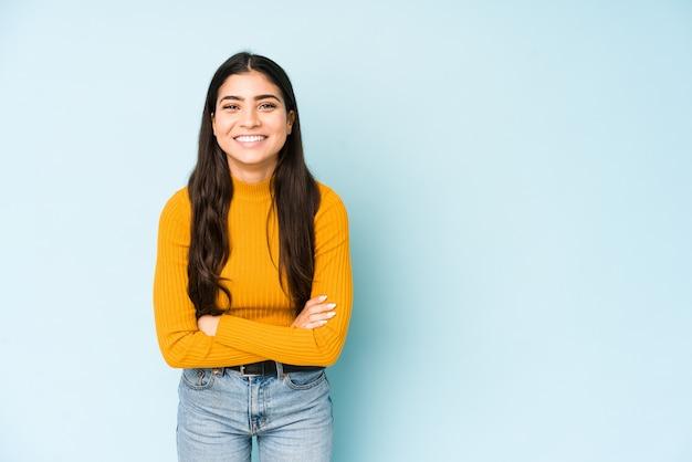 Giovane donna indiana sulla parete blu che ride e che si diverte.