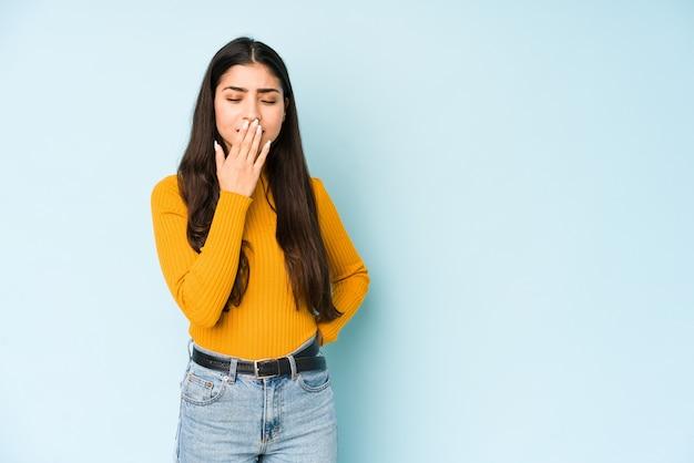 Giovane donna indiana sulla parete blu che sbadiglia mostrando un gesto stanco che copre la bocca con la mano.