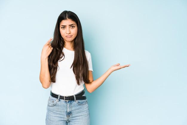 Giovane donna indiana sulla parete blu che tiene e che mostra un prodotto a portata di mano.