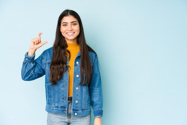 Giovane donna indiana sulla parete blu tenendo qualcosa di piccolo con gli indici, sorridendo