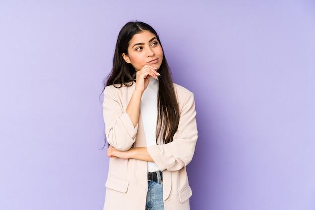 Giovane donna indiana sulla parete viola che guarda lateralmente con espressione dubbiosa e scettica.