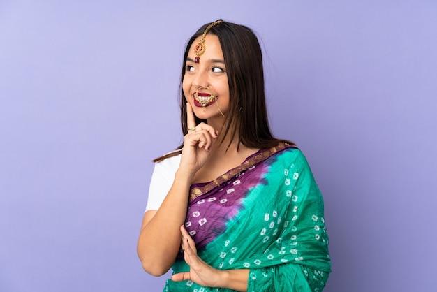 Giovane donna indiana sulla parete viola che pensa un'idea mentre osservando in su
