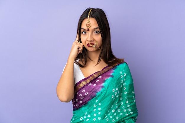 Giovane donna indiana sulla parete viola che pensa un'idea