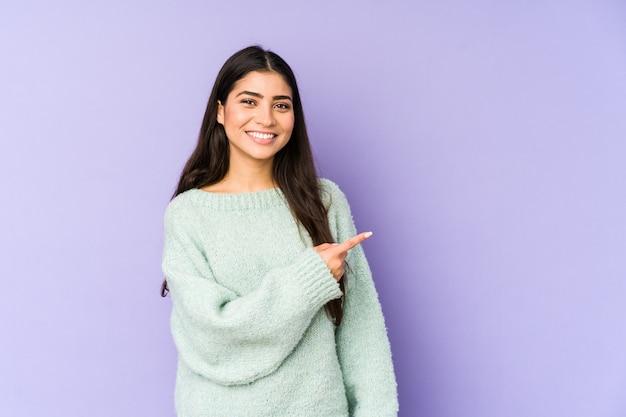 Giovane donna indiana sulla parete viola che sorride e che indica da parte, mostrando qualcosa nello spazio.