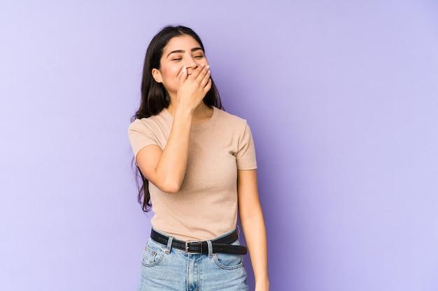 Giovane donna indiana sulla risata viola della parete felice