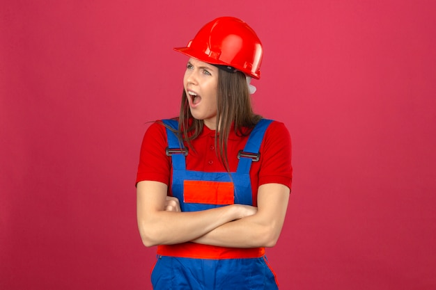 Giovane donna indignata in uniforme di costruzione e casco di sicurezza rosso in piedi con le mani incrociate su sfondo rosa scuro