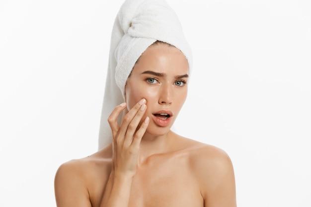 Giovane donna infelice che trova un'acne su una guancia. isolato su sfondo bianco