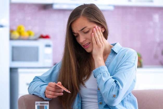 Giovane donna infelice sollecitata triste che prende gli antidolorifici dal mal di denti acuto a casa. dolori ai denti e problemi ai denti