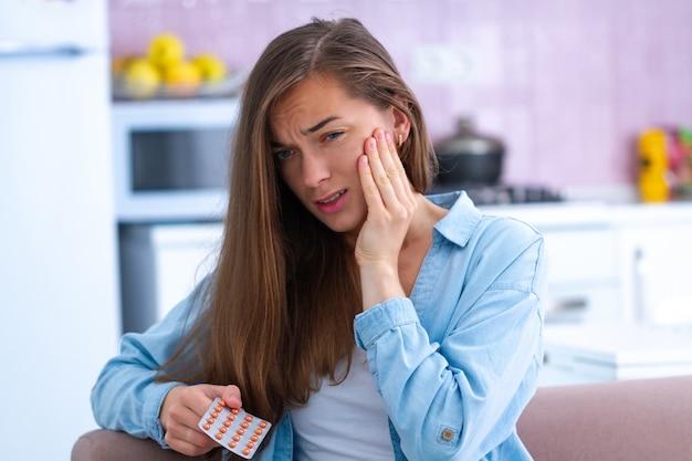 Giovane donna infelice triste che prende gli antidolorifici dal mal di denti acuto a casa. dolori ai denti e problemi ai denti