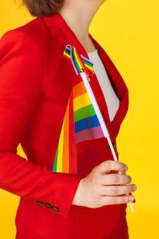 Giovane donna irriconoscibile che tiene piccola bandiera lgbt