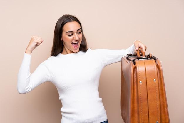 Giovane donna isolata sopra in possesso di una valigetta vintage