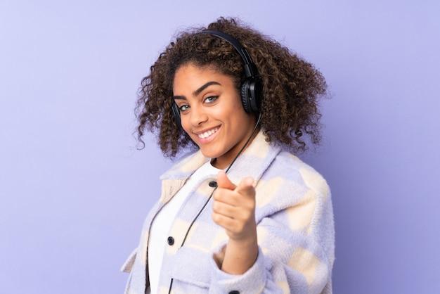 Giovane donna isolata su musica d'ascolto della parete viola e che indica la parte anteriore