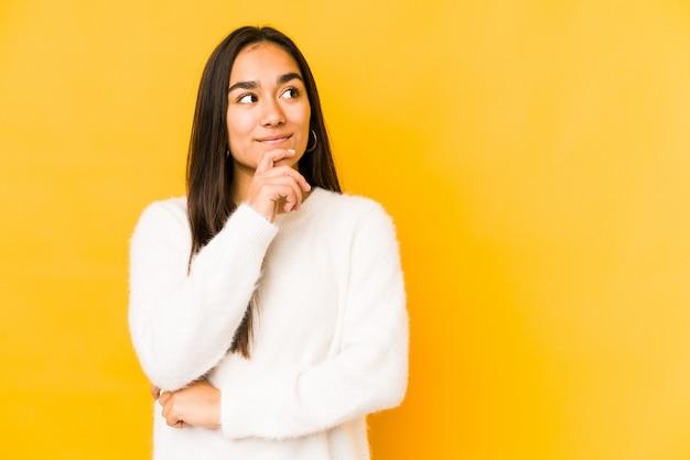 Giovane donna isolata su una parete gialla che guarda lateralmente con espressione dubbiosa e scettica.