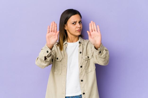Giovane donna isolata sulla condizione porpora con il segno di arresto di rappresentazione della mano tesa, impedendovi.