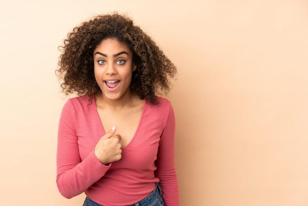 Giovane donna isolata sulla parete beige con espressione facciale di sorpresa