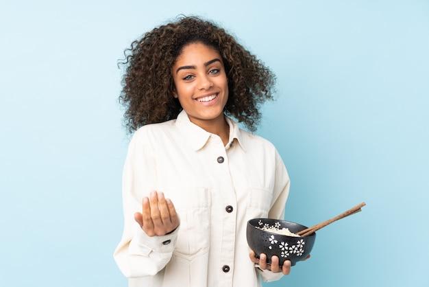 Giovane donna isolata sulla parete blu che invita a venire con la mano. felice che tu sia venuto con in mano una ciotola di noodles con le bacchette
