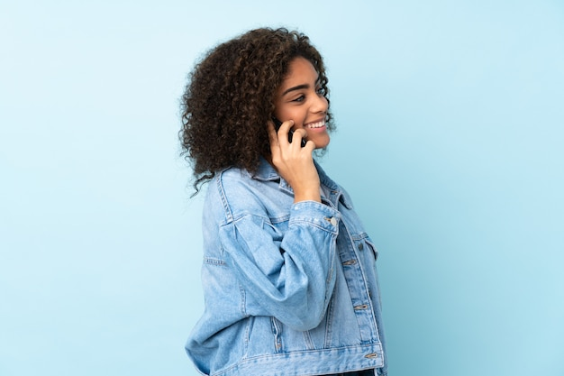 Giovane donna isolata sulla parete blu mantenendo una conversazione con il telefono cellulare con qualcuno